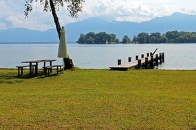 table with benches and pier on lake bank in view of beautiful mountains, germany, chiemsee