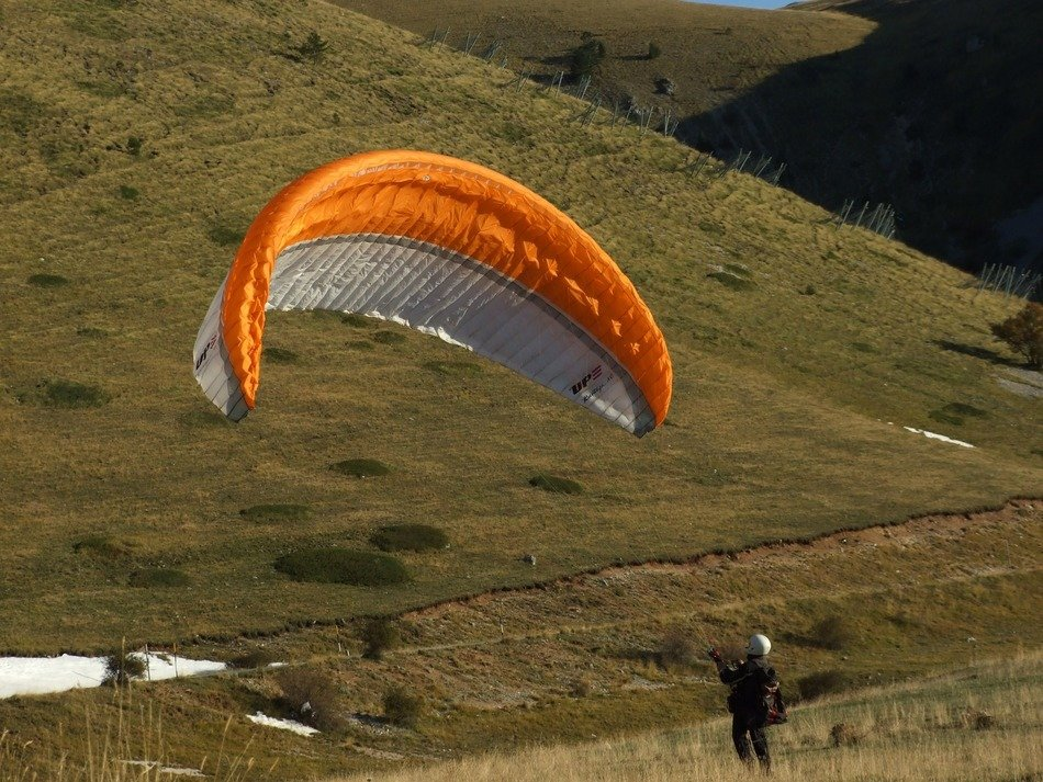 paraglider on a background of green mountains