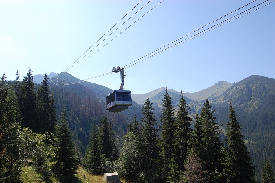 cable car in the mountains above green trees