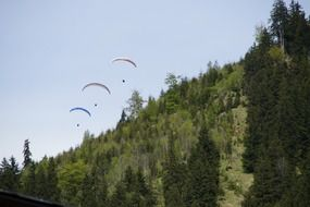 skydivers fly over the mountain