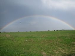 beautiful rainbow over a green rural field