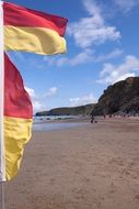Red and yellow flags on a beach