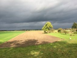gray storm clouds over the arable field