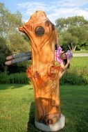 child playing on a wooden sculpture