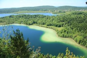top view of blue lake in green forest, france, jura