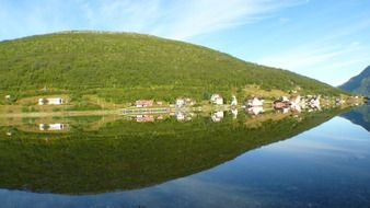 picturesque landscapes of norway are reflected in the water on a clear sunny day