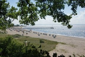 lot of cabins and long pier on beach of baltic sea