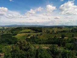 scenic green countryside beneath fluffy clouds, italy, chianti