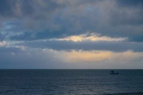 photo of a fishing boat in the ocean against the evening sky in Brazil