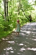 girl is walking along a forest path