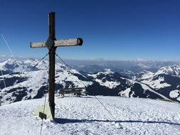 wooden cross on top of a snowy mountain