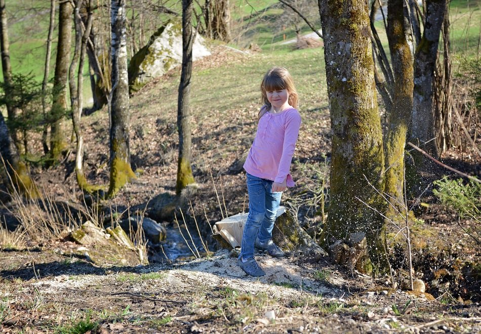 human child girl blond in the spring forest