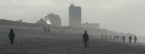 people walking on beach at sea on wintry foggy weather, germany, sylt