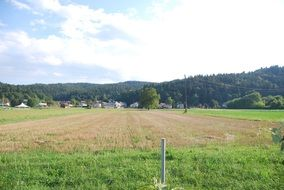 panorama of an agricultural field on a background of green hills