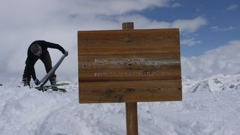 man on a snowy mountain near a wooden sign