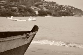 black and white photo of a fishing boat on the beach