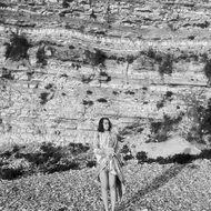 black and white photo of a girl on the beach near the cliff