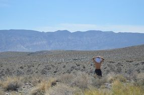 person stays in desert looking at mountains, usa, california