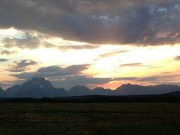 clouds above distant mountains at sunset, usa, Wyoming, Grand Teton National Park