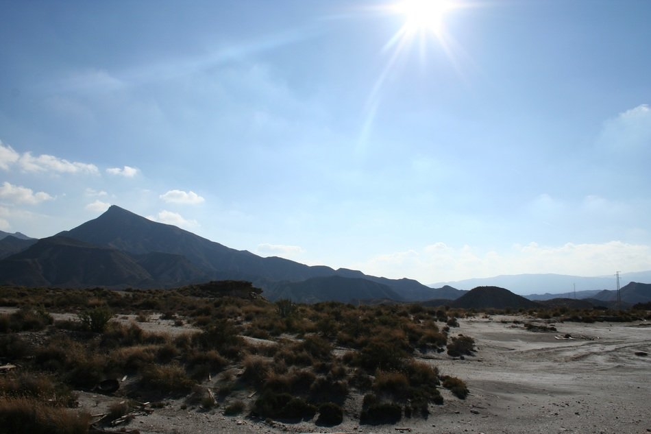 A picturesque desert against the background of volcanic rocks in the glare of the sun