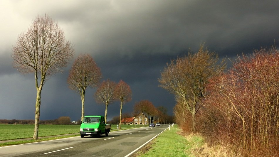 Auto on the road against a stormy sky