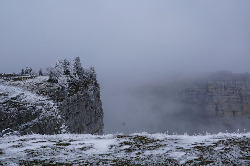 landscape of creux du van abyss in the fog
