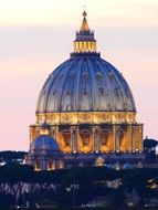 illuminated dome of st peter's basilica at pastel colored evening sky, italy, rome, vatican