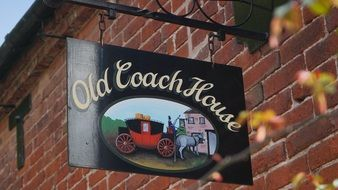 hotel sign Old coach house on a brick wall