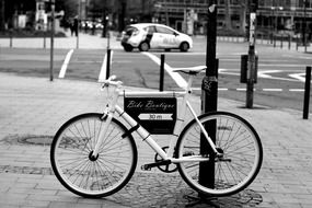 black and white photo of a bicycle near a post on the street
