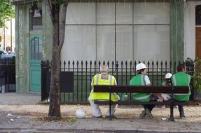 builders are sitting on a bench