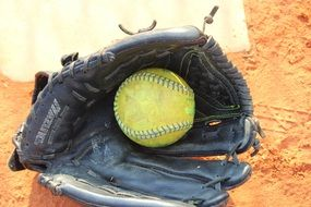 softball ball in leather glove on sand