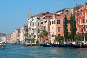 row of gondolas at waterfront in old city, italy, venice
