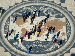 "A view from above of people on the monument ""map of the world"" in Lisbon"