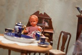 creepy old toy sitting by a tea table