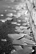 black and white photo of broken glass on the pavement