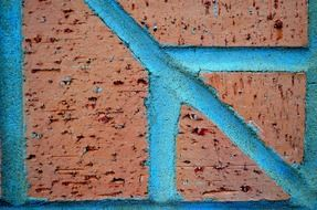 red brick wall with blue concrete stripes