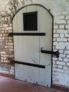 white wooden door with wrought-iron lock