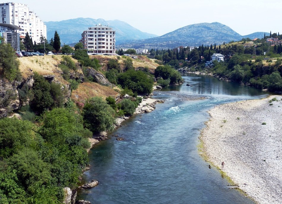 city at river in mountain landscape with green trees, montenegro, podgorica