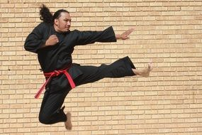 a man with red belt and black suit demonstrating a kick