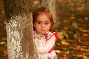 baby girl in a dress looking from behind a tree