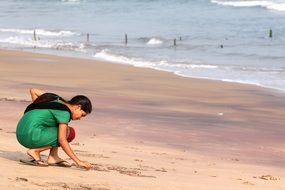 Indian girl bent to the sand near the ocean