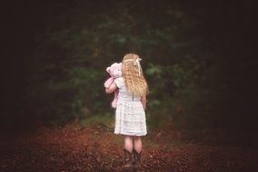 a view from the back on the little girl with pink teddy bear in the hands outdoors