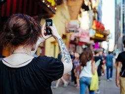 girl takes a picture of a city street on a mobile