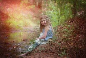 Happy baby girl sitting in a forest near the water