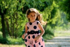 little girl is running in pink dress