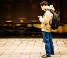 young man with smartphone and backpack on train station platform