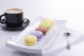 macaroon on a square plate and a cup of coffee