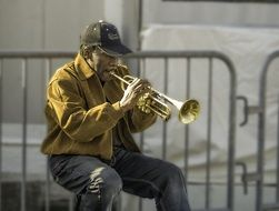 man on street playing trumpet