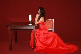 girl in a red dress on a background of burning candle on a table