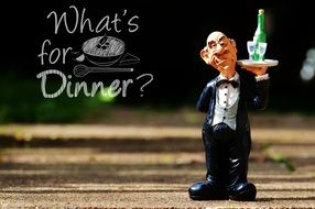 "figurine of the funny waiter with a tray on a background inscription ""what's for dinner?"""